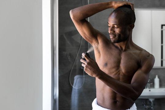 smiling african american man in towel holding deodorant spray in bathroom