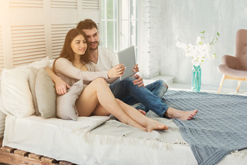 Happy couple with tablet in bedroom at home