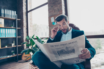 Portrait of surprised smart funny funky bearded intelligent curious handsome chief wearing smart suit old-fashioned jeans touching glasses reading news from newspaper at workplace