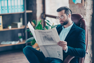 Side profile view half-turned view photo of serious successful concentrated confident handsome virile masculine modern employee sitting on armchair reading financial newspaper at work place