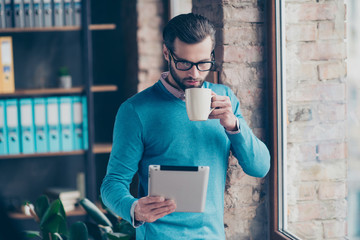 Portrait of concentrated confident clever intelligent busy banker dressed in formalwear blue pullover checkered shirt enjoying tea reading new using digital tablet standing near window at workstation