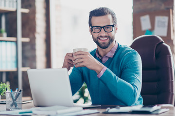 Stunning, smiling,  manly IT-manager in glasses, pullover, shirt, sitting on leather chair at desktop in workplace, looking at camera, holding mug with tea