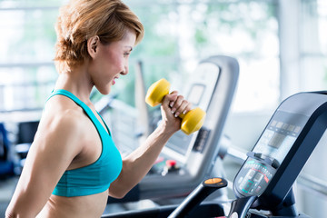 Shorthaired young woman doing exercises with dumbbells as additional weight while walking on treadmill in gym