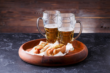 Photo of two mugs of beer and hot dogs on wooden tray