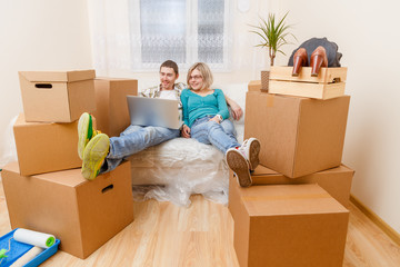 Photo of couple sitting on couch with laptop among cardboard boxes