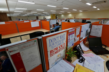 Employees work at their desks inside Tech Mahindra office building in Noida