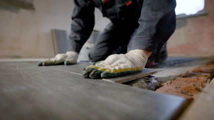 Close look at the constuction worker laying down the tile on cemented floor. Fototapete
