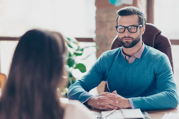 Job interview - Serious successful businessman listen carefully to candidate answers, sitting at desktop in work place on armchair