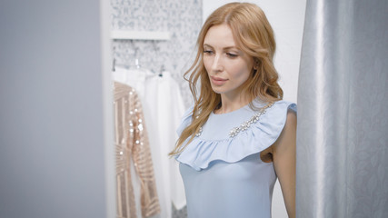 sensual girl with wavy hair is trying on a blue trendy dress in a fitting room in clothing store and admiring of herself in mirror
