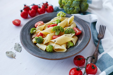 Pasta penne with broccoli on white wooden table. Healthy vegetarian food.