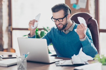 Angry, disappointed, crazy accountant in pullover holding crumpled paper in hand, looking at laptop with clenched teeth, sitting on armchair at desktop in work place