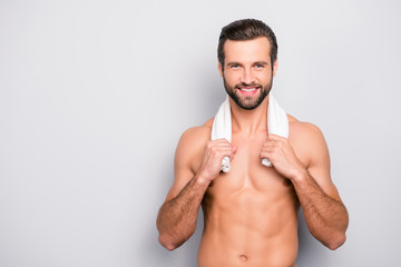 Portrait of confident stunning athletic sporty guy holding towel on neck, he is going to take a morning shower, isolated on grey background with copy space