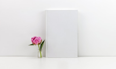 White book mockup with a pink peony flower