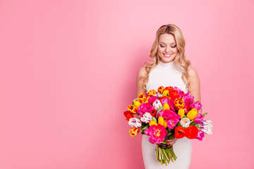 Portrait with copy space empty place of charming pretty woman in white dress having big bouquet of tulips in hands looking at flowers isolated on pink background