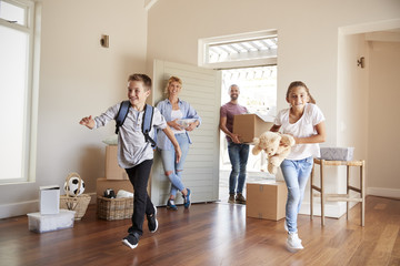 Excited Family Carrying Boxes Into New Home On Moving Day Fototapete
