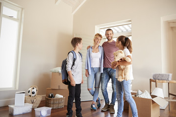 Excited Family In Lounge Of New Home On Moving Day