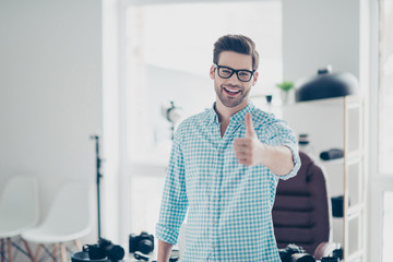 Portrait of positive cheerful guy in shirt with stubble and modern hairstyle standing in photo studio, laughing,  gesturing thumb up to the camera