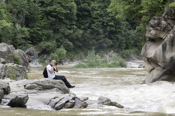 Young man takes pictures on the bank of a stormy river. Sunny summer day