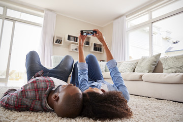 Couple Lying On Rug And Posing For Selfie At Home