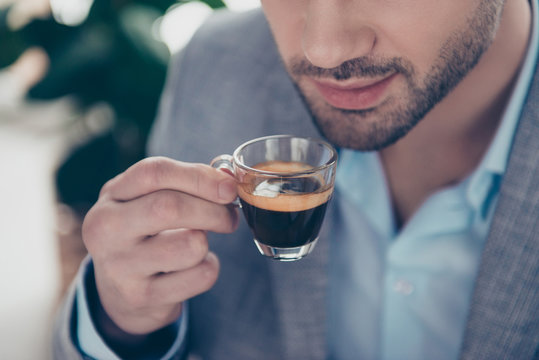 Cropped close up half face portrait of stylish attractive man holding small glass with espresso near mouth, every morning ritual before work in work place