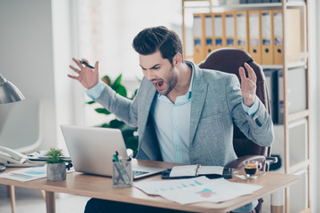 Portrait of rage boss is out of himself, gesturing with hand, yelling at screen of computer, having hard day, problems, troubles with work, sitting at desktop in work place