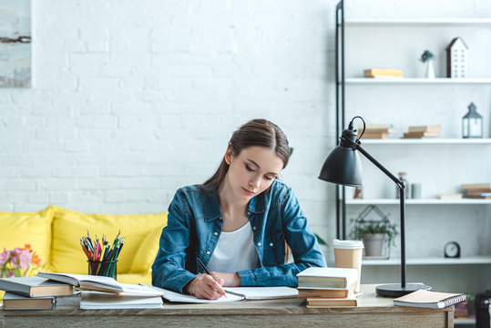 concentrated teenage girl writing and studying at desk at home