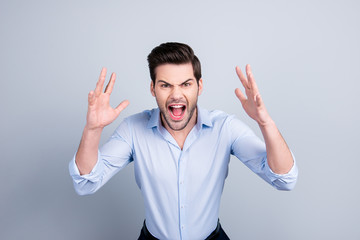 Portrait of very angry annoyed man out of himself, shouting, yelling, holding hands near face, standing over grey background