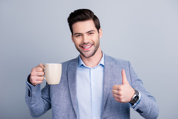 Portrait of cheerful positive manager showing thumb up symbol with hand and holding mug of tea, looking at camera, isolated on grey background