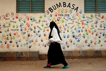 A woman walks past a wall painted by soccer fans, ahead of the 2018 FIFA World Cup in Russia, in the Lyari neighborhood in Karachi