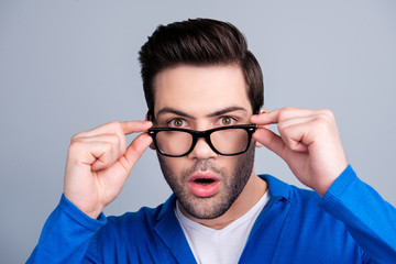 Portrait of amazed man looking out glasses, holding eyelets with two hands, having open mouth, isolated on grey background, dressed in blue pullover