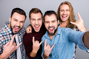 Birthday rock and roll leisure music playing band hobby trip concept. Four mad virile masculine brutal handsome bearded excited guys gesturing horns, casual checkered outfit isolated gray background