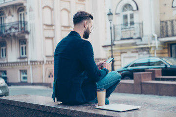 Rear vie portrait of busy concentrated man sitting outside holding smart phone in hands chatting with friends during coffee break pause