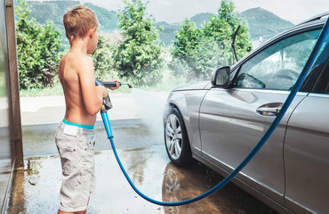Boy helps to wash a car
