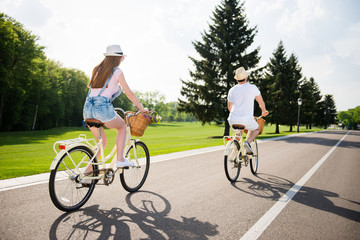 Rear back view of athletic beauitful traveler riding on bikes in park enjoying fresh air green grass big trees. Delight harmony recreation inspiration travel tourism healthy lifestyle concept
