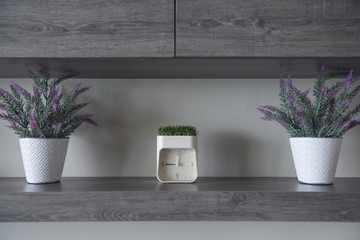 Wooden shelf interior with flowers and clock