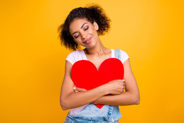 Portrait of cute sweet girl keeping eyes closed hugging big carton paper heart figure enjoying festive card from lover isolated on yellow background