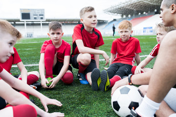 Portrait of group of eager teenage boys sitting in circle listening to motivational pep talk from coach before team practice in outdoor stadium