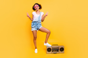 Fullbody portrait of positive cheerful girl in jeans jumpsuit eyewear sneakers having boom box gesturing two v-signs enjoying favorite song stereo sound isolated on yellow background