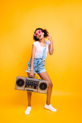 Full body portrait of positive laughing girl in eyewear jumpsuit holding boom box in hand gesturing rock and roll sign isolated on yellow background. Party maker music lover fan hobby concept