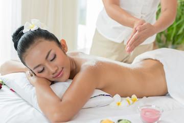 Woman enjoying getting a salt scrub beauty treatment at spa.