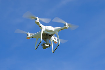 Flying quadrocopter close-up against the blue sky