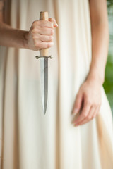 woman's hands holding a sharp knife, close up concept, can be used as background