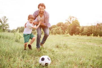 Father is playing football with his son. They are running down the meadow. Boy is hugging his dad and looking at ball. Man is doing the same thing.