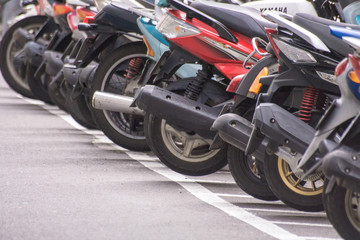 Taipei, Taiwan - June 10, 2018 : A row of motorcycle parking along the roadside in Taipei's street,...