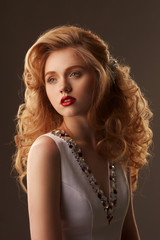 Fashion beauty studio portrait of young beautiful pretty woman with makeup, red lips and updo hairstyling. Stunning girl with golden hair. Photo in warm colors.