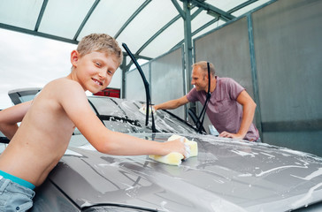 Boy helps his father to wash a car, simply home work child help