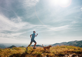 Man runs with his beagle dog on mountain top