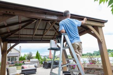 Handyman on a ladder staining a backyard gazebo