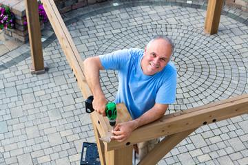 Friendly man erecting a new wooden gazebo