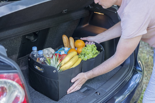 Man puts in the trunk of a car bag basket full of products